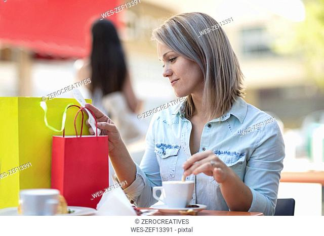 Woman with shopping bags at an outdoor cafe checking bill