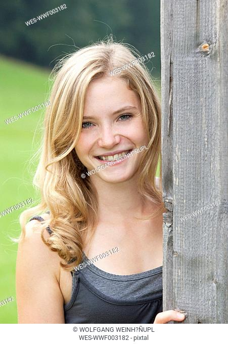 Austria, Salzkammergut, Mondsee, portrait of young woman leaning at grey wooden facade
