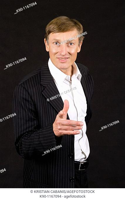 Caucasian man with friendly pose, pointing with his finger at the camera, studio shot