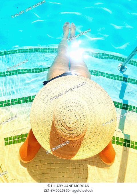 View from above of young woman in sunhat sat on swimming pool steps