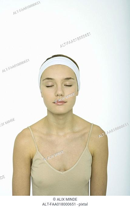 Teenage girl wearing headband, eyes closed