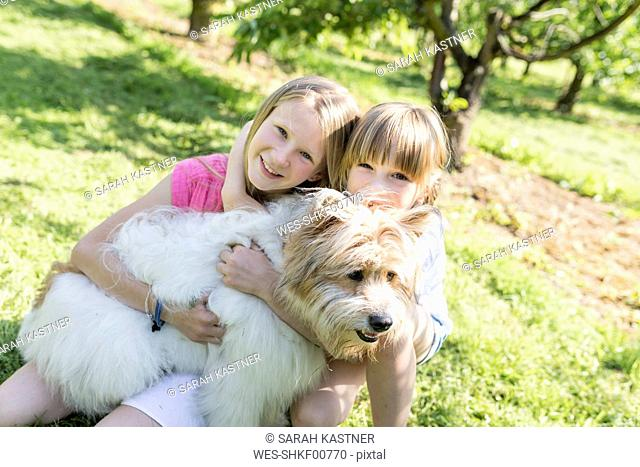 Two smiling sisters cuddling with dog on meadow
