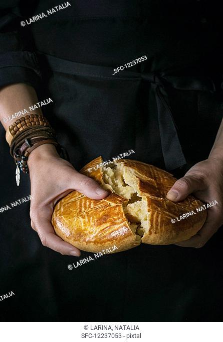 Homemade traditional armenian sweet cake gata in female hands over black background