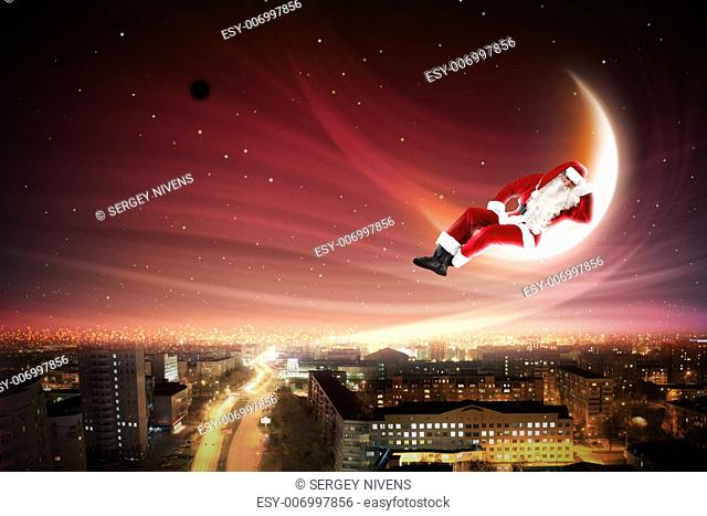 Santa Claus on the moon above a city at night