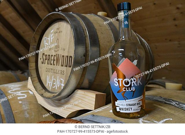 A bottle of Stork Club stands next to a barrel at the storage of the Spreewood Distillers in Schlepzig, Germany, 26 July 2017