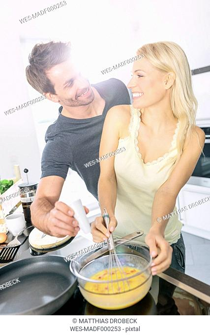 Couple preparing scrambled eggs together in the kitchen