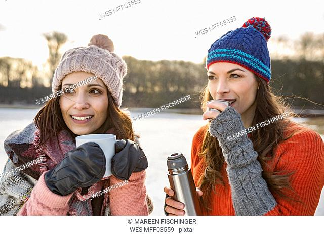 Two women drinking hot beverages outdoors in winter