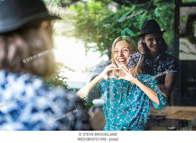 Beautiful young woman making a finger frame heart and smiling at her boyfriend through a window