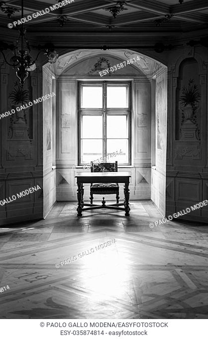 A solitaire chair and table in an ampty room of Castle Savoia, building in typical Walsen architectural style