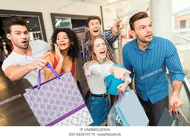 Sale in black Friday. The company of young people are engaged in shopping on a black Friday. Guys and girls saw a big sale at the showroom