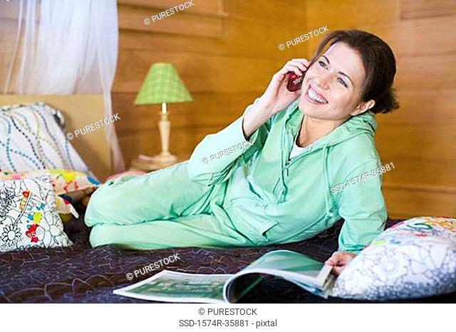 Woman reclining on bed and using mobile phone
