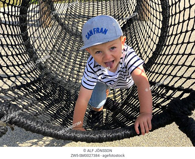 Boy, thee years old, plays in a net on a playground in Ystad, Sweden, Scandinavia