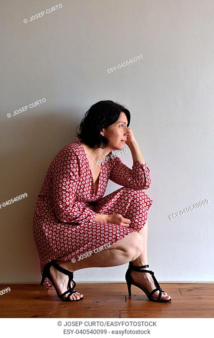 woman sitting squatting in front of ura wall