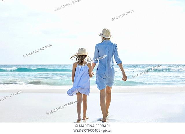 Mother and daughter walking by the sea, rear view