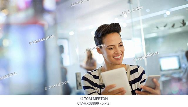 Smiling creative businesswoman using smart phone and digital tablet