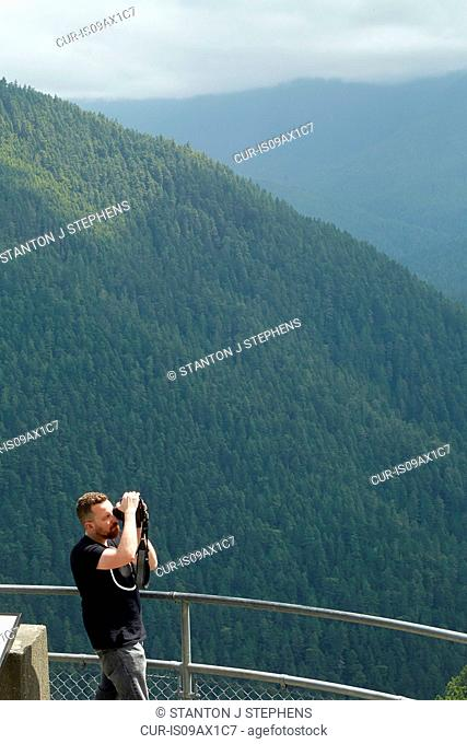 Male photographer photographing forest from viewing platform, Olympic Mountains, Washington State, USA