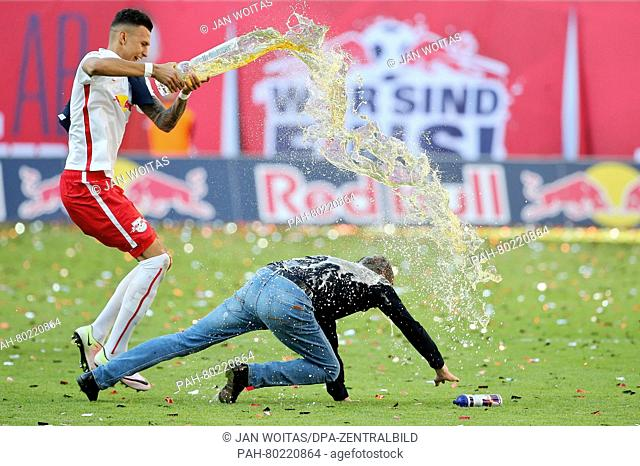 Leipzig's Davie Selke pours beer on coach Ralf Rangnick to celebrate the team's promotion to the 1st Bundesliga after the German 2nd Bundesliga soccer match...