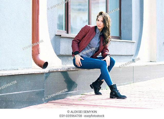 Young beautiful stylish woman in a burgundy pilot's jacket and blue jeans, street style, spring and autumn trend, look, hair in the wind