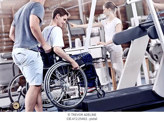Physical therapists guiding man in wheelchair on treadmill