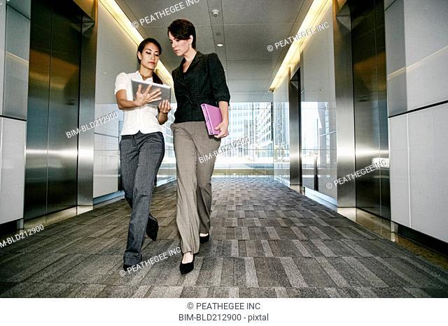 Businesswomen using tablet computer in lobby