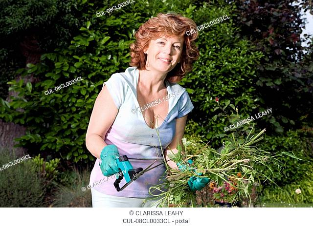 Mature woman holding plants in garden