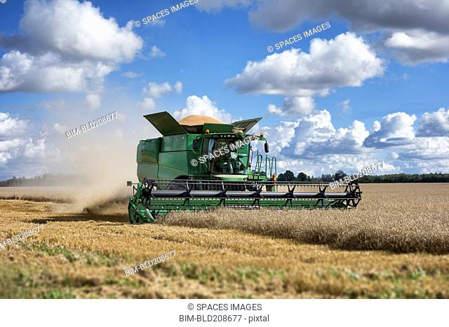 A large combine harvester machinery cutting the ripe arable crop