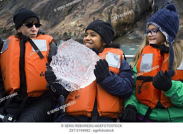 Passengers of Safari Endeavour cruise playing with a big ice at Fords Terror, Endicott Arm, Tongass National Forest, Alaska, USA