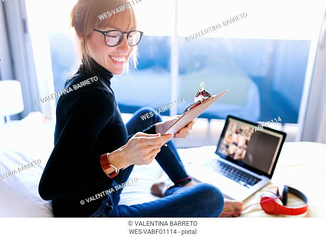 Smiling young woman on bed with clipboard and laptop