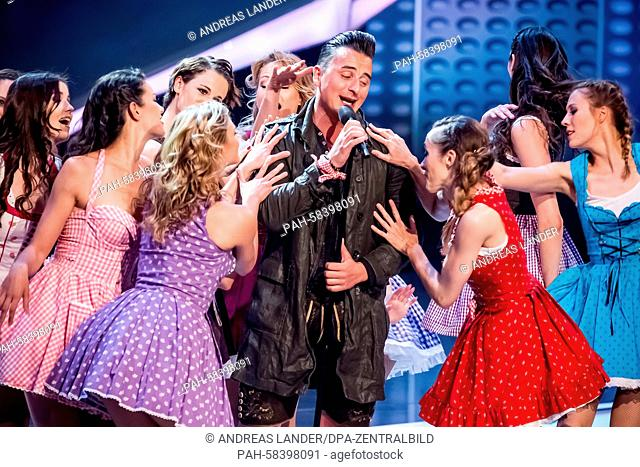 Austrian singer Andreas Gabalier (C) performs on stage with members of the 'Deutsche Fernsehballett' dance ensemble during the German television show...