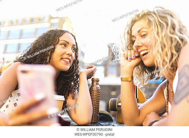 Two happy friends sharing cell phone outdoors