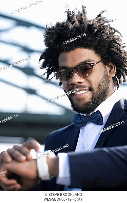 Smiling young man with sunglasses looking at his smartwatch