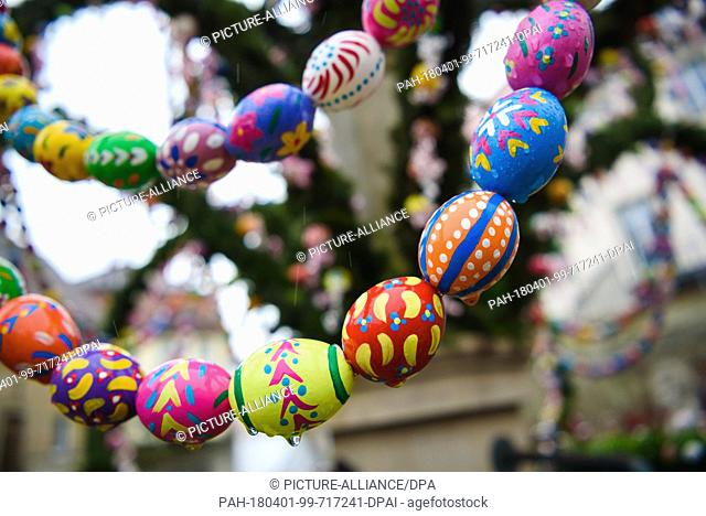 01 April 2018, Germany, Zeil am Main: Rain drops on painted easter eggs at the Easter well in Zeil am Main in Lower Franconia