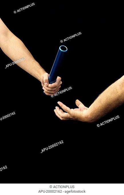 Two athletes passing a baton