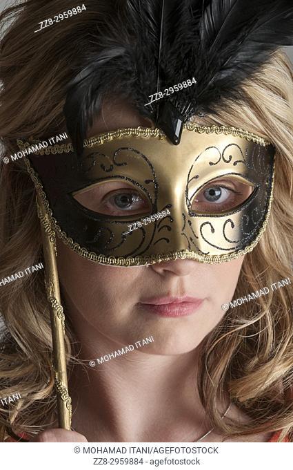 Portrait of a blonde woman wearing a Venetian mask