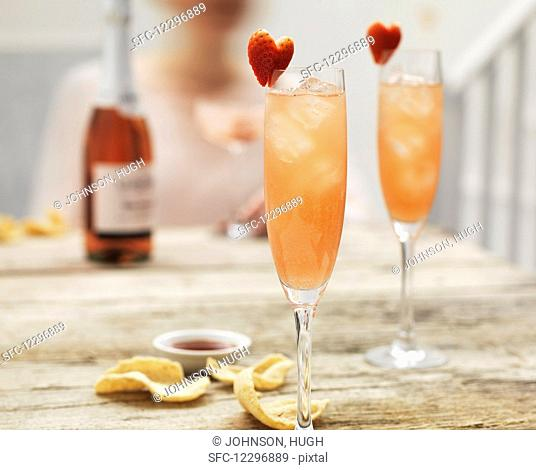 Champagne cocktails with hibiscus and strawberry hearts