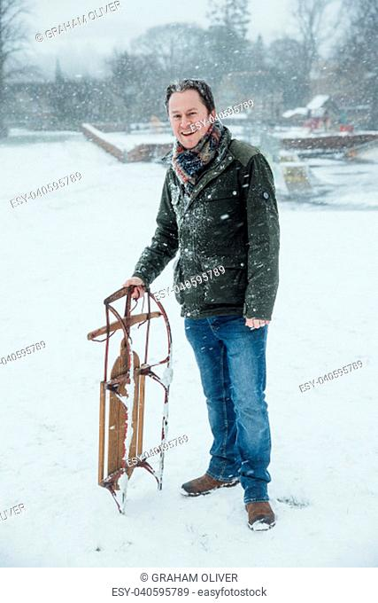 Mature man is smiling for the camera while standing outdoors in the snow, holding a sleigh