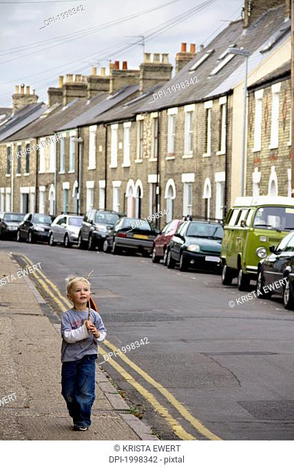 a young boy walks down the street with a stick, cambridge united kingdom