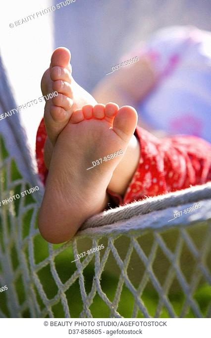 Close up of a girl's feet resting on a hammock