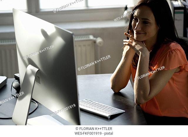 Businesswoman sitting in office, working on computer