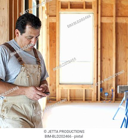 Hispanic construction worker text messaging on cell phone in unfinished room