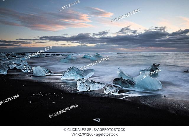 A winter sunset from Jokulsarlon black beach in southern Iceland, depicted at long exposure to enhance the wave motion and pattern