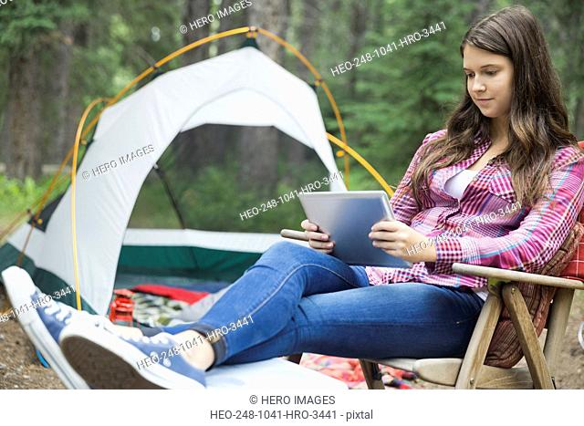 Teenage girl using digital tablet at campsite