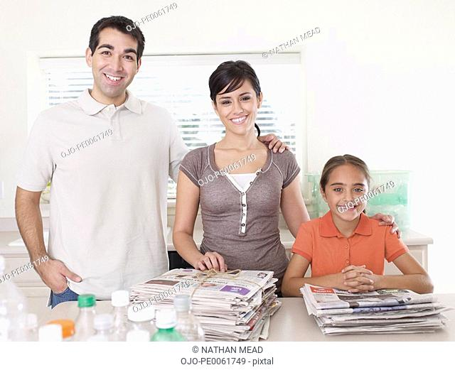 Couple and young girl standing in kitchen with recyclable materials smiling