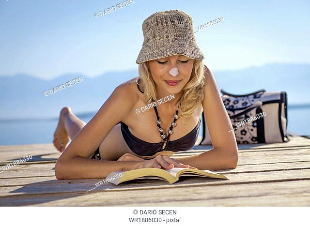 Croatia, Young woman with straw hat reading book on beach