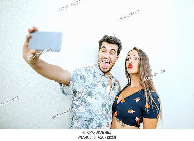 Playful couple taking a selfie with smartphone in front of white wall