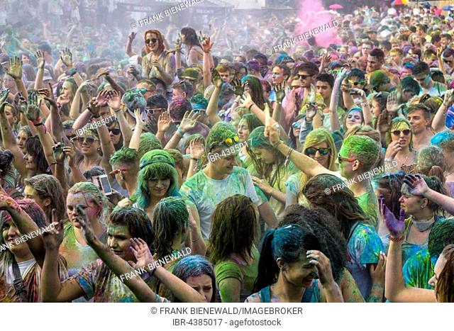 Thousands of young women and man are raising their arms at the colorful Holi festival, Dresden, Saxony, Germany