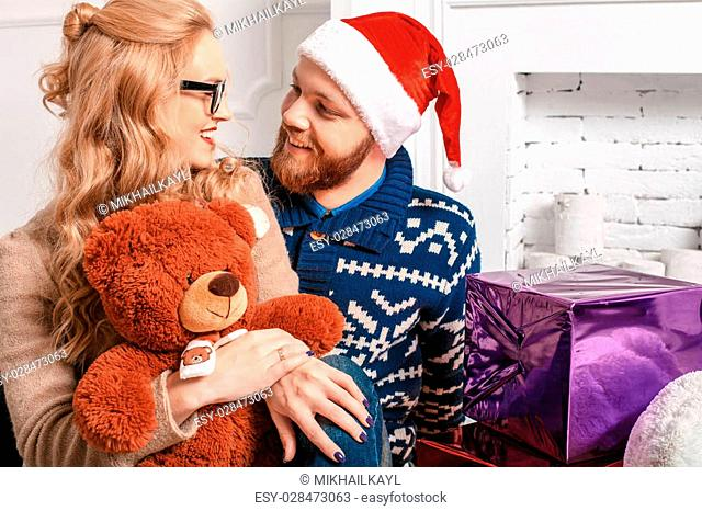 Beautiful couple in Santa hat with gifts by the fireplace. Merry Christmas background