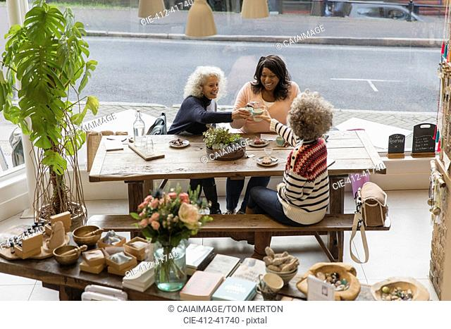 Women friends toasting teacups at cafe shop