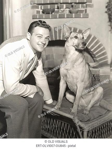 Young man sitting with dog at home (OLVI007-OU845-F)