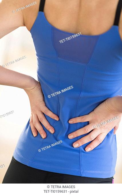 Midsection of woman with hands on back